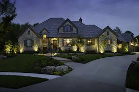 awesome residential landscape lighting on the front yard of luxury residential house with stone wall complete with lawn and rocks plus garden lamps also
