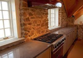 kitchen with a rustic rock like backsplash and concrete countertops
