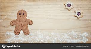 wooden panel with gingerbread man and star shaped cookies stock photo
