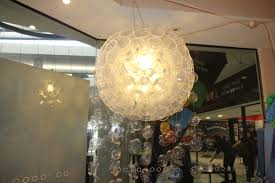 a chandelier made out of plastic cups and the bottom of plastic bottles hangs