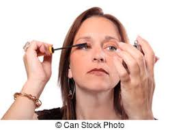 woman holding hand mirror. Woman Holding Hand Mirror Applies Mascara To Eyelashes