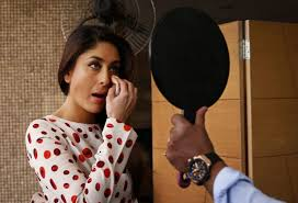 bollywood actor kareena kapoor retouches her makes up in a mirror held up by a male