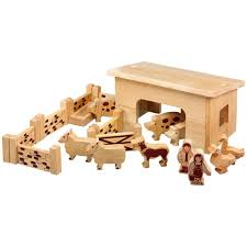 natural wood smaller barn building with farm animals people walls fences and gates
