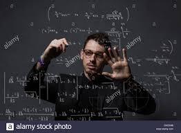 man writing mathematical equations on glass wall stock image