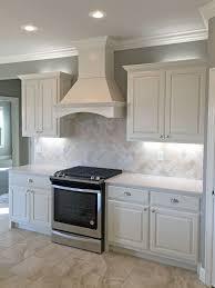 White kitchen with satin nickel fixtures, pendant lights, travertine  backsplash, white quartz countertops, wood range hood The husband was  thinking of ...