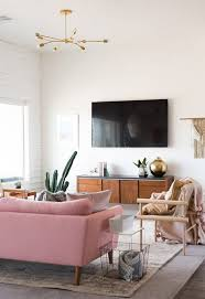 lighting for living rooms. midcentury inspired living room design with plenty of brass and pops pink lighting for rooms