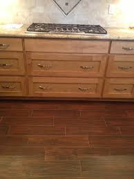 remodel old kitchen design with ceramic tile flooring that looks like wood planks and oak cabinet with white marble countertop for narrow kitchen ideas