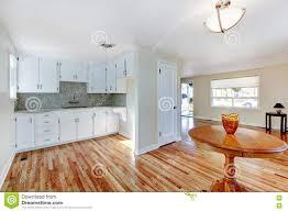 White Kitchen With Hardwood Floors White Kitchen Cabinets With Light Tone Hardwood Floor Stock Photo
