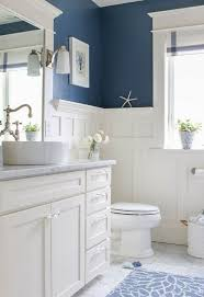 white wainscoting matches the furniture and appliances and creates a fresh feel with blue walls