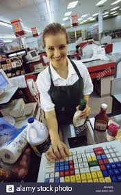 portrait of a female s clerk working on a cash register at a portrait of a female s clerk working on a cash register at a supermarket checkout counter