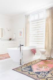 your house chic white bathroom features a freestanding tub and floor mount tub filler placed in the center of the room flanked by pink and blue rugs