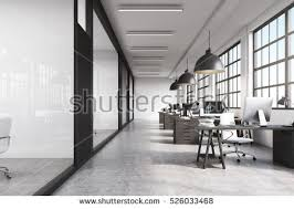 floor office. front view of a long office room with concrete floor tables desktops and