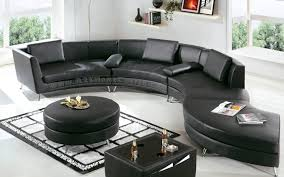 s shaped black sofa and black cushions with black round table