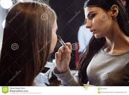 preparation to the photoshoot serious young brunette makeup artist using a cosmetic brush and allying makeup while working with a model