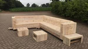 In this picture a simple structure of wooden pallet sofa is shown which is  placed outdoor and it is not yet ready to use because it is not ready  completely.