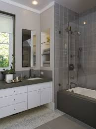 incredible mosaic floor tiles featuring shower barrier glass enclosure and white bathroom vanity with drawers and dark gray granite countertopounted