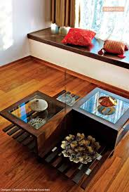 wooden centre table with glass work near the bay window