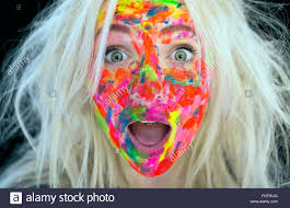 woman with messy blonde hair and face covered in multi coloured paint with a surprised expression