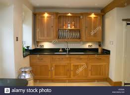 Lighting Above Wooden Kitchen Cupboards With Built In Sink In Modern
