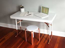 With a quick coat of paint, it's a cinch to turn a boring and blah plastic folding  table into a chic, minimalist desk.
