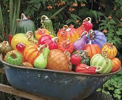 a wheelbarrow full of glass pumpkins on display during the cohn stone studios spring garden