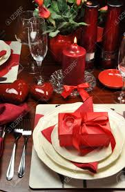 red valentine romantic dinner for two table setting with gift candle and hearts vertical