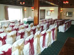 alternating burdy and gold organza bows on white chair covers