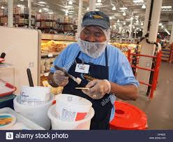 costco and employee stock photos costco and employee stock a n american male employee of costco whole dispensing food samples new york