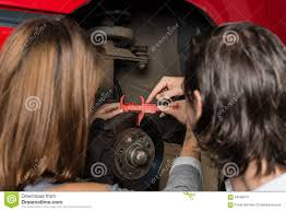 auto mechanic and female trainee changing a car stock photo auto mechanic and female trainee changing a car