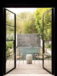 steel french doors open onto the deck with woven chairs either side of a white garden stool overlooking the pool framed by a slate waterfall backdrop