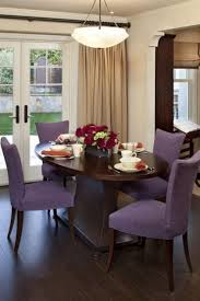 room small wooden dining table between the purple upholstered dining chairs under white curtains around door purple chairs the color is on the chair