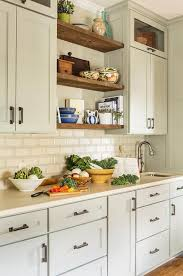 gray kitchen features light gray shaker cabinets topped with cream quartz countertops and cream beveled subway tiles walker zanger alhambra beveled brick