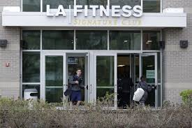 a person leaves an la fitness gym while a group of women enter the club
