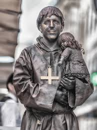 a living statue is a street artist who poses as a statue or mannequin usually