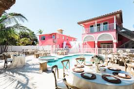 reception decor for retro inspired beach villa poolside wedding with wooden chairs and floating white and pink tropical bouquet with wild greenery siesta