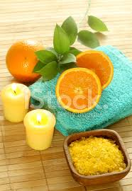 bath salt in wooden bowl towel candle and fresh orange