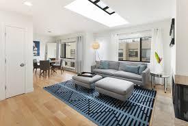 small modern living room with gray sofa skylight and light wood floors