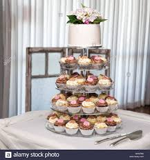 Tier Of Cupcakes And Wedding Cake Topped With Flowers Stock Photo