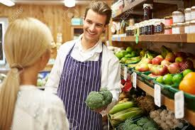 assistant helping customer at vegetable counter of farm shop stock assistant helping customer at vegetable counter of farm shop stock photo 31019750