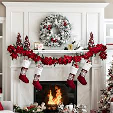 Large white fireplace decorated with a snow-flocked wreath, poinsettias,  Christmas cards,