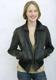 teenage girl standing with hands in pockets smiling portrait