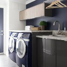 gray lacquered laundry room cabinets with blue front load washer and dryer