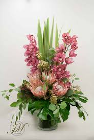 Tall vase display made of cymbidium orchids, proteas, wax flowers and  foliage.