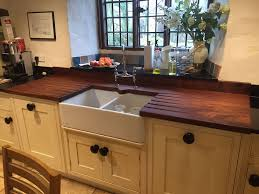 we red the wooden sink surround and draining area in a character farmhouse kitchen by removing old cuts and sanding the surface before painting with a