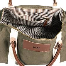 opened view green canvas and leather duffle bag w personalized leather name plate