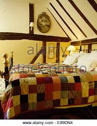 Colourful patchwork quilt on bed in country bedroom with large ... & ... Colourful patchwork quilt on old brass bed in beamed cottage bedroom -  Stock Photo Adamdwight.com