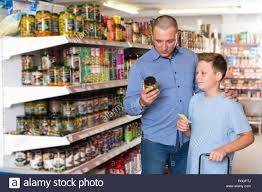 Grocery Store Product List Portrait Of Father And Boy Choosing Goods With Shopping List In