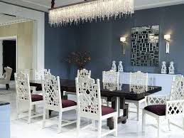 rectangle crystal chandelier over long rectangular dining table with classic dining chairs front of accent