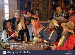 Saloon niñas mirando un cowboys mano de cartas que está jugando al póquer  en el bar Fotografía de stock - Alamy