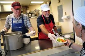 volunteers joe sommers left and jorge is serves lunch to clients at the thomas